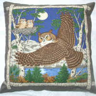 Eagle owl in flight on a moonlit night with two chicks in a nest cushion