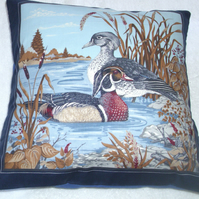 Wood Ducks in the water by a river bank cushion, blue edging