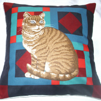 Ginger Tabby cat sitting on a multi coloured background cushion