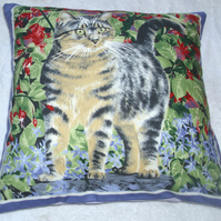 Lovely grey Tabby cat by a red fuchsia bush in the garden cushion