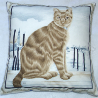 Ginger tabby cat sitting on a quayside cushion