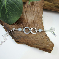 Sterling Silver Infinity Knot Bracelet with Aquamarine. Adjustable Fit