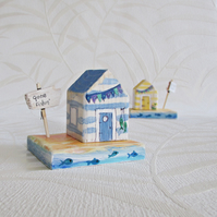 A Little Wooden Beach Hut House, on a base and a wooden sign.