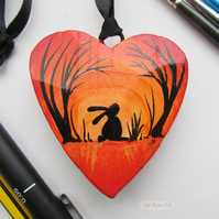 Hare or Rabbit silhouette by sunrise, orange hanging heart