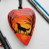 Wolf silhouette by sunrise, orange hanging heart
