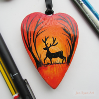 Stag silhouette by an Autumnal sunrise, orange hanging heart