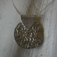 Round silver pendant with leaf bail