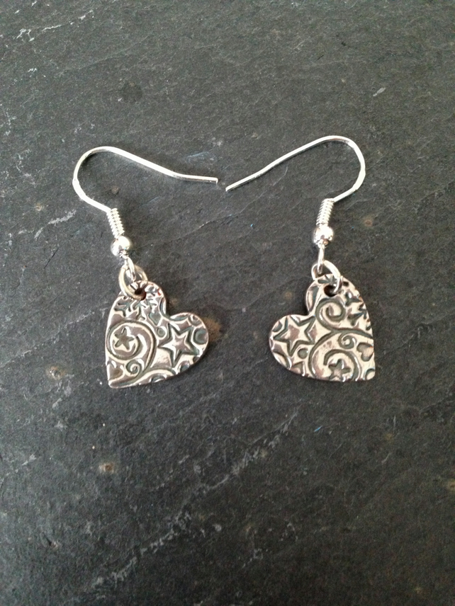 Silver heart earrings with star and swirl impression
