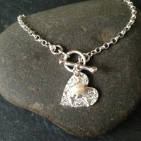 Silver heart charm bracelet finished with a freshwater pearl
