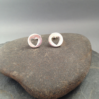Small round silver studs with a heart cut out