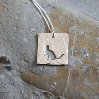 Silver cat pendant: A cut cat sits with one paw out ready to swat a toy