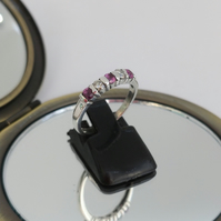 Pink sapphire and moissanite half eternity ring.