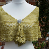 Shawl hand knit in a crescent shape using a green yellow coloured soft yarn