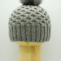 "Hand Knitted ""Honeycomb"" faux fur pom-pom hat in grey"