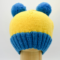 Hand knitted Child's hat in yellow and turquoise blue with two pompoms