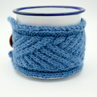 White enamel camping mug with hand knitted mug cosy in blue