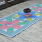 Petal Power Fabric Quilted Table Runner with dark green backing.