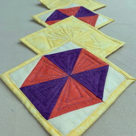 Set of four quilted coasters with a traditional hexagon patchwork design.