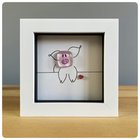 A box framed picture of a cheeky, pink fused glass pig