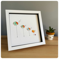 Group of glass birds picture in a box frame with birds in a range of heights