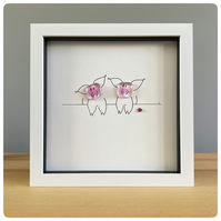 A pair of cheeky, pink fused glass pigs in a box frame