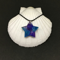 Star blue and violet resin and ink pendant with black cord.