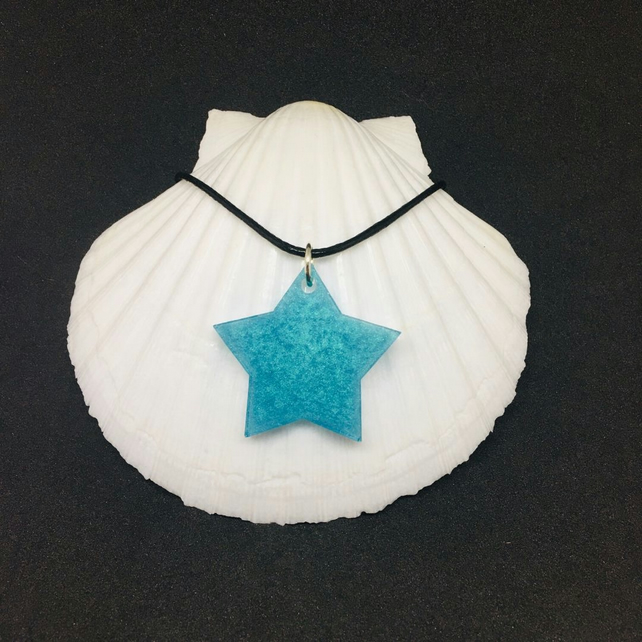 Turquoise star pendant on a black cord necklace.