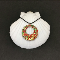 Red green and gold sparkly donut necklace encased in resin.