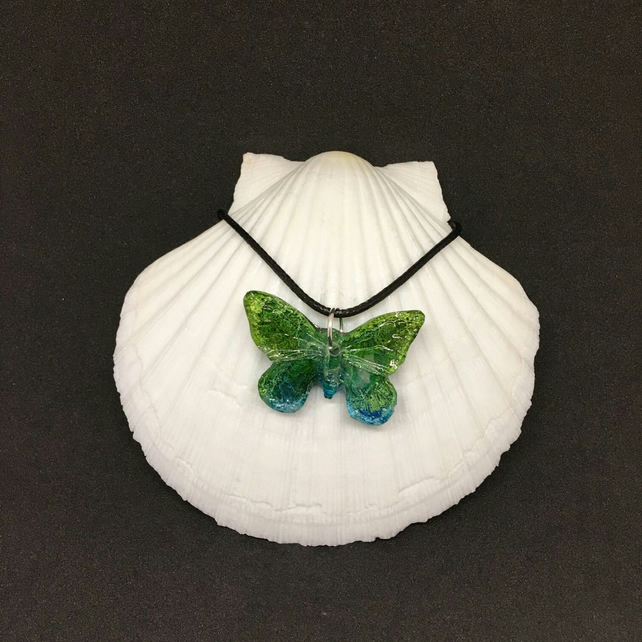 Green and blue butterfly resin and ink necklace.