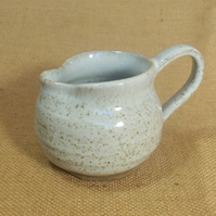 Stoneware  jug with speckled white glaze.