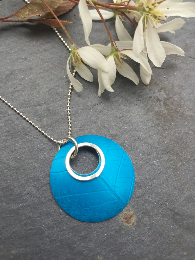 Turquoise, circular, leaf textured, anodised aluminium pendant with silver ring