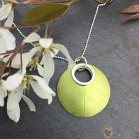 Circular anodised aluminium leaf textured pendant with silver ring.