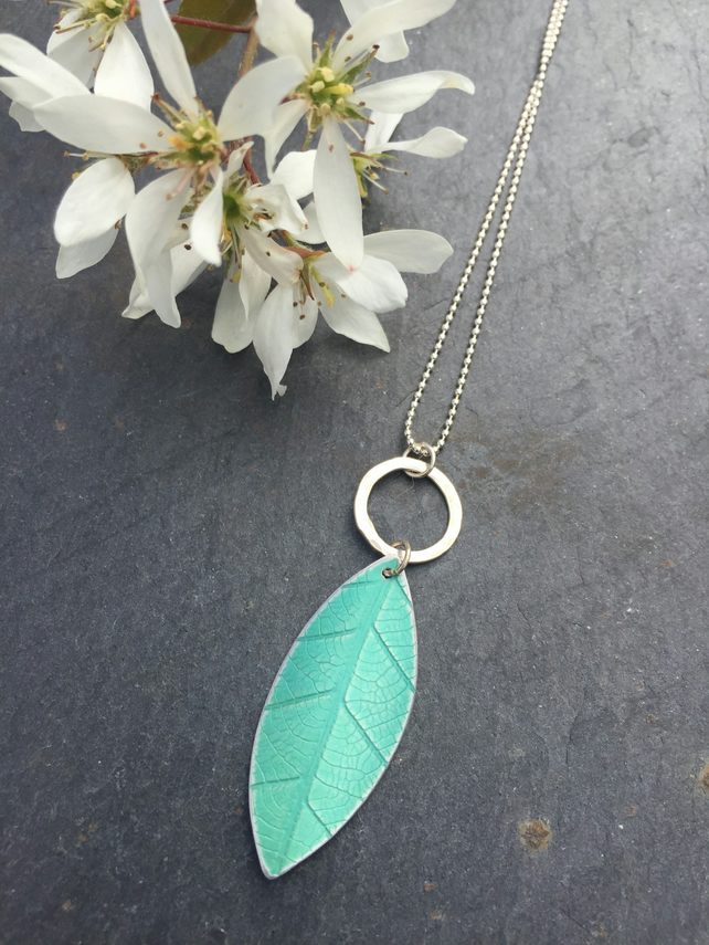 Soft green, anodised aluminium distressed leaf pendant with silver ring.