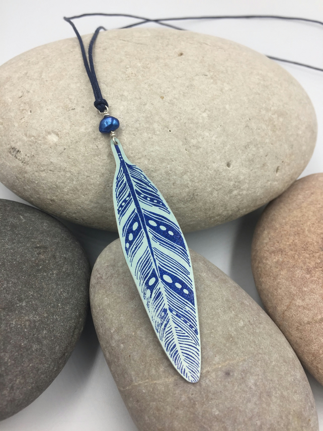 Long length hand printed anodised aluminium feather pendant in navy blue