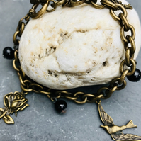 Vintage  style charm bracelet with vintage black beads, key,bird,& flower