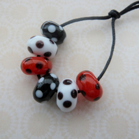 handmade lampwork glass beads, red and black spots