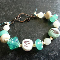 green bird lampwork and copper bracelet