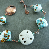 sand dollar lampwork glass and copper bracelet