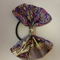 Hair bobble bow in purple pattern fabric.