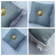 Pin cushion in blue with white trim and button.