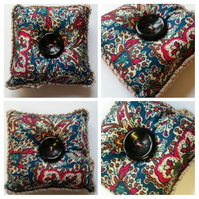 Pin cushion in teal and cherry red pattern fabric.