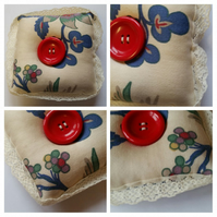 Pin cushion in cream floral fabric.