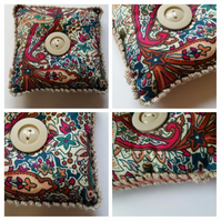 Pin cushion in teal and cherry red fabric.