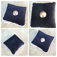 Pin cushion in black corduroy with silver trim and button.