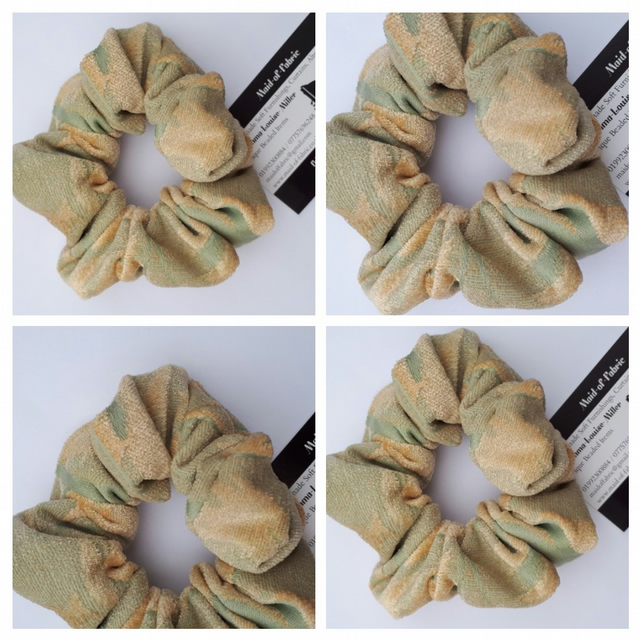 Hair scrunchie in green and cream fabric.