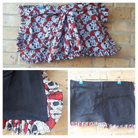 Black denim apron pinny with skull frills and pockets.