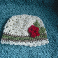 Crochet hat - with christmas rose and holly leaves.
