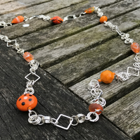 Orange glass beads and silver chainmaille long necklace