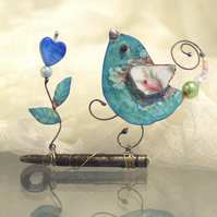 Birdie on key with glass heart.
