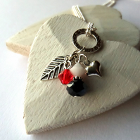 Cluster necklace with leaf and heart charms, and red Swarovski® crystal
